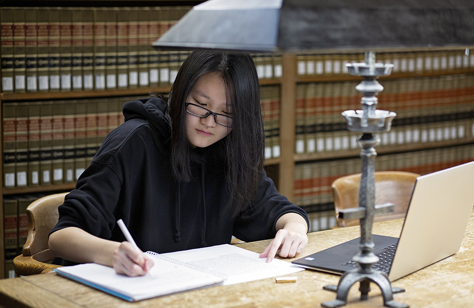 Student working on notes in library